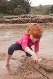 Little red haired girl building a sand castle with wet sand at a Royalty Free Stock Photo