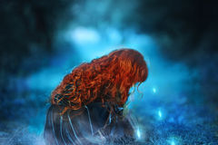The little red-haired girl looking at the glowing lights Stock Photo