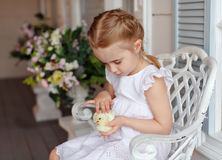 The little red-haired girl with pigtails holding a yellow chicke Royalty Free Stock Images