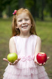 Little red-haired girl in a pink dress holding two apples Royalty Free Stock Photography