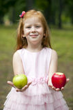 Little red-haired girl in a pink dress holding two apples Stock Photography