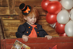 Little red-haired girl in a retro circus. Clown Royalty Free Stock Photo