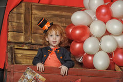 Little red-haired girl in a retro circus. Clown Stock Photography