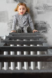 Little red-haired girl sitting on a stairs Stock Photos