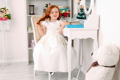 Little red haired girl in white dress Royalty Free Stock Image