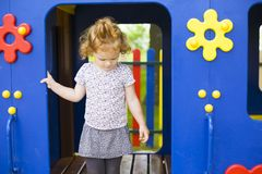 Little red-haired girl in a wooden house for children on the playground royalty free stock image