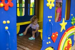 Little red-haired girl in a wooden house for children on the playground royalty free stock images