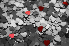 Little red hearts. Among grey hearts royalty free stock photography