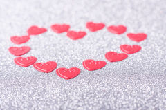 Little red hearts. Compose big one on silver glitter background Stock Photography