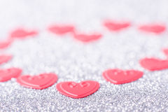 Little red hearts. Compose big one on silver glitter background Royalty Free Stock Image