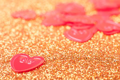 Little red hearts. On golden glitter background Royalty Free Stock Photos