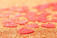 Little red hearts. On golden glitter background Royalty Free Stock Photo