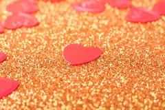 Little red hearts. On golden glitter background Stock Image