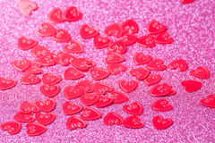 Little red hearts. On pink glitter background Stock Images