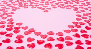Little red hearts. Shape big one on pink background Royalty Free Stock Image