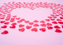 Little red hearts. Shape big one on pink background Royalty Free Stock Images