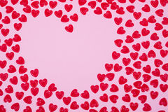 Little red hearts. Shape big one on pink background Stock Image