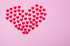 Little red hearts. Shape big one on pink background Royalty Free Stock Photography