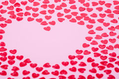 Little red hearts. Shape big one on pink background Stock Photography