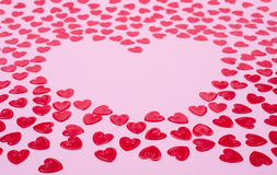 Little red hearts. Shape big one on pink background Stock Images