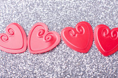 Little red hearts. On silver glitter background Royalty Free Stock Photography