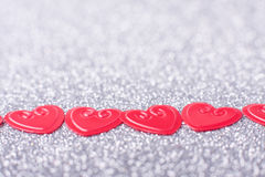Little red hearts. On silver glitter background Royalty Free Stock Image