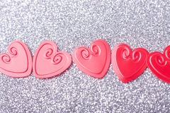 Little red hearts. On silver glitter background Stock Images