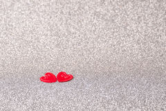 Little red hearts. Two little red hearts on silver glitter background Royalty Free Stock Image