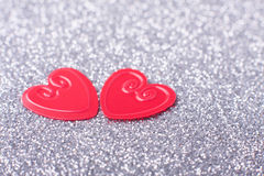Little red hearts. Two little red hearts on silver glitter background Stock Images
