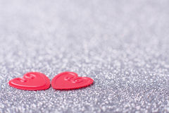 Little red hearts. Two little red hearts on silver glitter background Royalty Free Stock Images