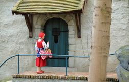 Little Red Hood near the door of a house in Theme Park Efteling. Spring