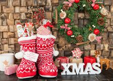 Little knitted boots with presents. Little red knitted boots with presents and treats for christmas Royalty Free Stock Images