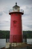 Little red lighthouse under Washington Bridge on overcast day stock photography