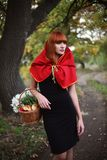 Little Red Riding Hood. The red-haired girl with a flowers basket. On a wood footpath Stock Photo