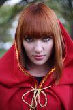 Little Red Riding Hood. Portrait of the red-haired girl in a red hood Royalty Free Stock Images