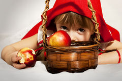 Little Red Riding Hood. Girl dressed as Little Red Riding Hood eating an apple Stock Images