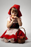 Little Red Riding Hood. A girl with a toy wolf wearing Little Red Riding Hood costume Stock Photo
