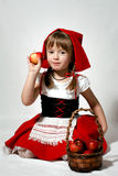 Little Red Riding Hood. A girl with a basket of red apples wearing Little Red Riding Hood costume Stock Images