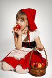 Little Red Riding Hood. Girl dressed as Little Red Riding Hood with basket of red apples eating an apple Royalty Free Stock Photos