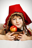 Little Red Riding Hood. A girl with a basket of red apples wearing Little Red Riding Hood costume Royalty Free Stock Image
