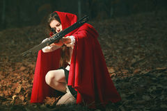 Little red riding hood aiming with crossbow stock photo