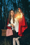 Little Red riding hood alone in the dark forest. Little Red riding hood lost in the forest at night holding a lantern Stock Photos