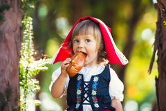 Little Red Riding Hood bites a patty in the forest. Little Red Riding Hood bites a patty in the forest Stock Photography