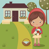 Little Red Riding Hood. Close to grandma's house with flowers and basket Royalty Free Stock Image