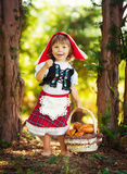Little Red Riding Hood in the forest carries pies in the basket.  Royalty Free Stock Photo
