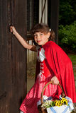 Little red riding hood knocking on door. Little red riding hood entering the cottage of her grandmother Stock Photo