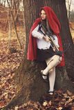 Little red riding hood waits her prey. Little red riding hood leaning to a tree and waiting her prey Stock Images