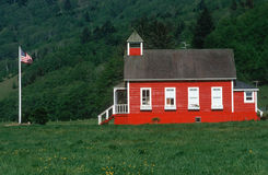 Little Red Schoolhouse. With American flag, Coastline, Oregon Stock Photo