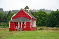 Little red schoolhouse. In meadow on misty morning Stock Image