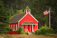 Little Red Schoolhouse with Flag. An old-fashioned little red schoolhouse in a forest area, with an American flag to the side Stock Photo